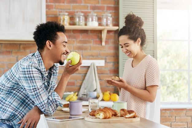 Une femme heureuse fait un sandwich, parle avec son mari qui est assis en face d'elle, mange des pommes. un couple de famille passe du temps libre ensemble,