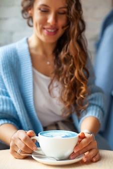 Femme heureuse floue avec de longs cheveux ondulés en pull chaud tenant une tasse de latte bleu chaud. boisson et couleur tendance. le thé au lait bleu est fait avec des fleurs de pois papillon. boisson aux herbes saine