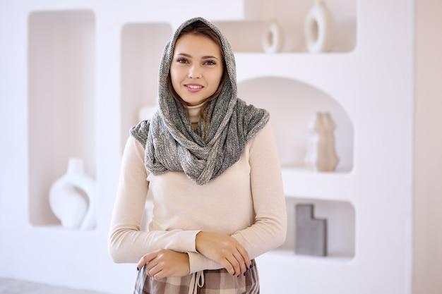 Une femme heureuse en foulard se trouve dans le salon