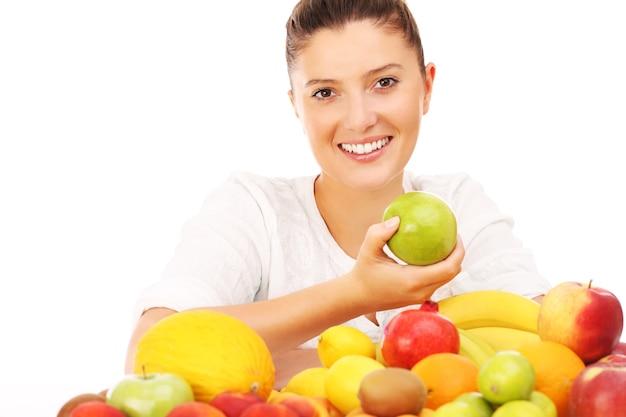 Une femme heureuse avec des fruits sur fond blanc
