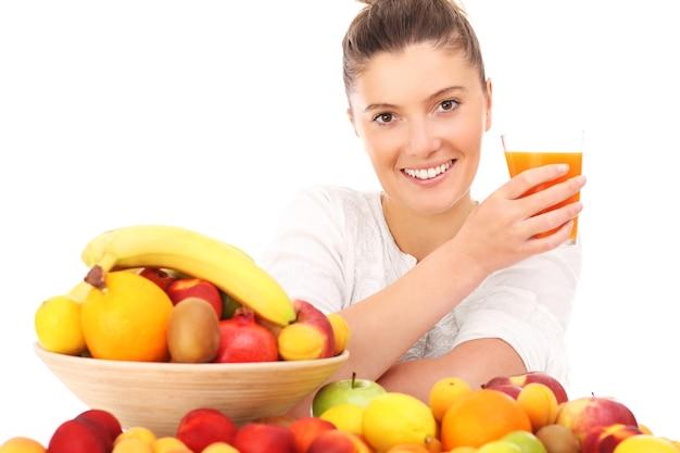 Une femme heureuse avec des fruits et un verre de jus sur fond blanc