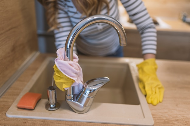 Femme heureuse en gants de protection nettoyage robinet avec chiffon à la cuisine à domicile