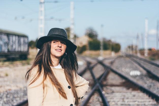 Femme heureuse en imperméable beige et chapeau sur les voies ferrées abandonnées.