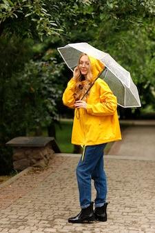 Femme heureuse en imperméable jaune avec parapluie transparent sous la pluie