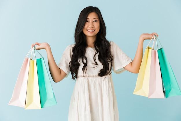 Femme heureuse isolée sur mur bleu tenant des sacs à provisions