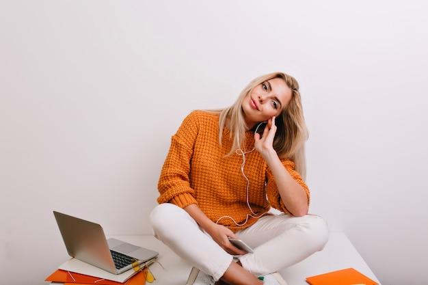 Femme heureuse en jeans blancs assis sur la table dans des écouteurs et se reposer après une dure journée de travail