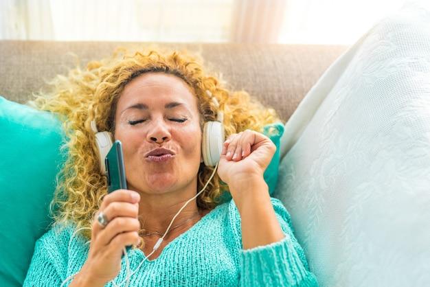 Une femme heureuse et jeune chantant et écoutant de la musique sur le canapé ou le canapé à la maison avec des écouteurs blancs - style de vie de musicothérapie