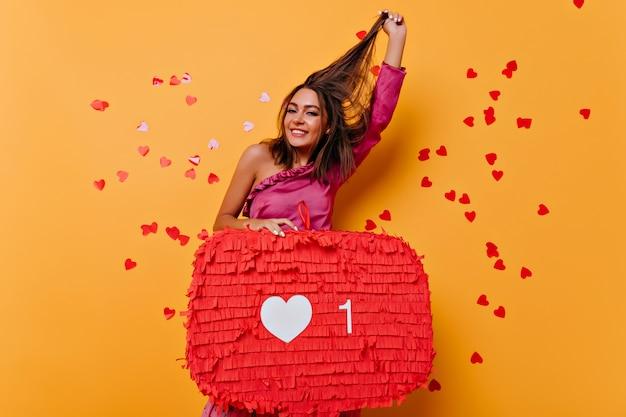 Femme heureuse jouant avec ses cheveux tout en posant avec la bannière. portrait de jeune fille profitant des réseaux sociaux sur jaune.