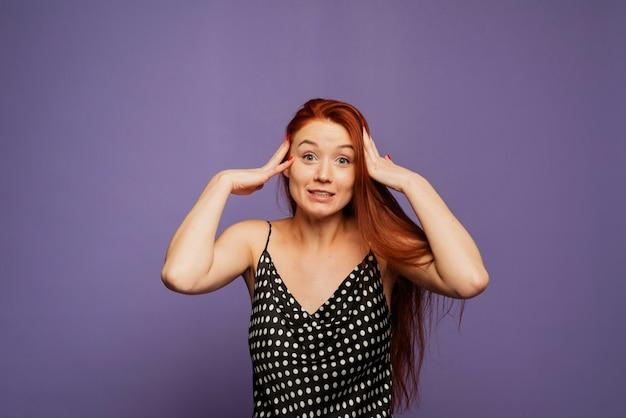 Une femme heureuse et joyeuse se réjouit de gagner, rit et est agréablement choquée. fille rousse émotionnelle dans une robe à pois noirs sur un mur de lavande lilas
