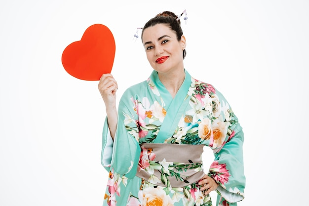 Femme heureuse en kimono japonais traditionnel montrant un coeur en carton sur blanc