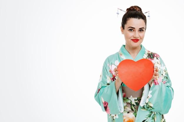 Femme heureuse en kimono japonais traditionnel montrant un coeur en carton souriant joyeusement sur blanc
