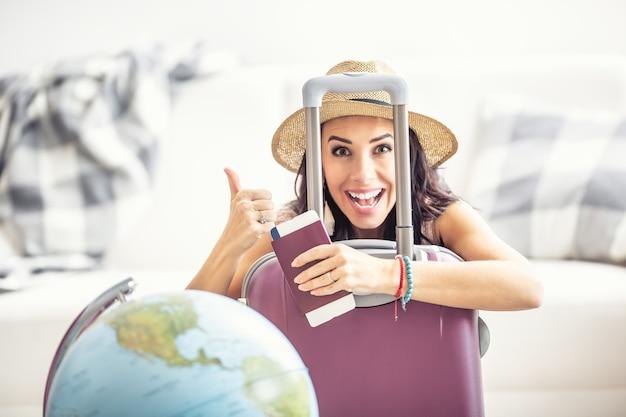 Une femme heureuse lève le pouce alors que les restrictions de voyage s'assouplissent et qu'elle peut à nouveau voyager, avec un passeport et un billet d'avion.