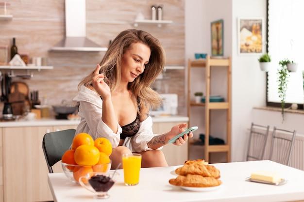 Femme heureuse en lingerie sexy défilant au téléphone pendant le petit-déjeuner dans la cuisine à domicile. jeune femme blonde séduisante en sous-vêtements sexy avec des tatouages assis dans une cuisine moderne.