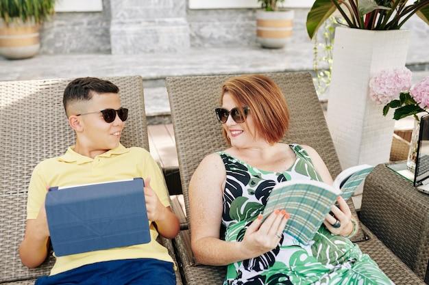 Femme heureuse avec livre dans les mains en regardant un fils adolescent avec tablette numérique reposant sur une chaise longue