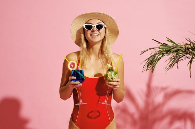 Femme heureuse en maillot de bain pose avec cocktails près de la paume sur rose