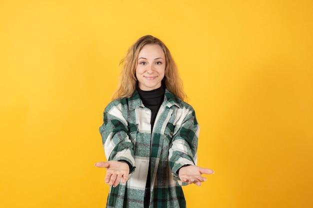 Femme heureuse avec les mains tendues vers l'avant sur une chemise à carreaux sur fond jaune