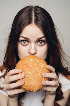 Femme heureuse, manger un hamburger