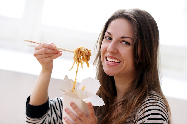 Femme heureuse, manger nouilles