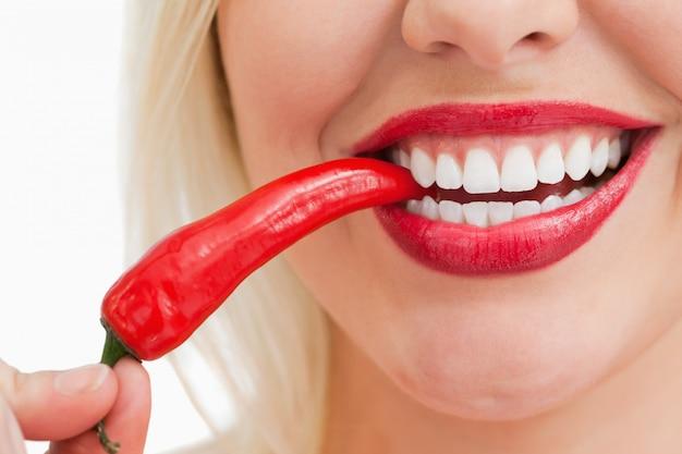 Femme heureuse, manger un piment rouge