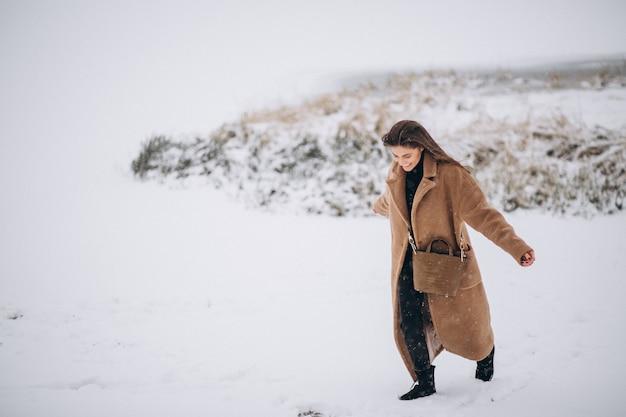 Femme heureuse en manteau en hiver dehors dans le parc