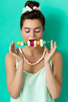 Femme heureuse avec maquillage coloré et bonbons sucrés sur brochette
