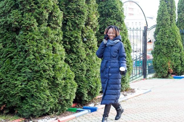 La femme heureuse marche dans la rue en hiver