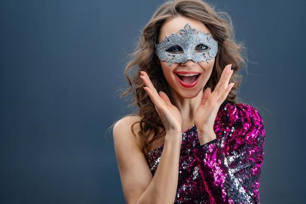 Femme heureuse en masque de carnaval et robe avec gros plan paillettes