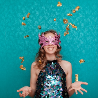 Femme heureuse avec masque rose et pluie de confettis