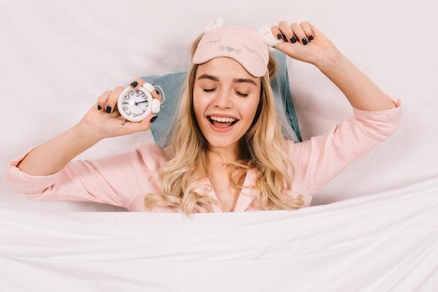 Femme heureuse en masque de sommeil rose posant dans son lit