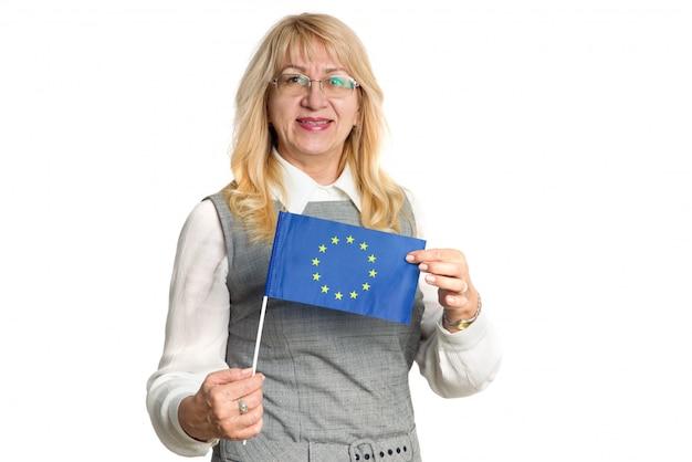 Femme heureuse mature dans des verres avec le drapeau de l'union européenne sur un fond blanc.