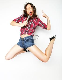 Femme heureuse avec microphone sautant et chantant