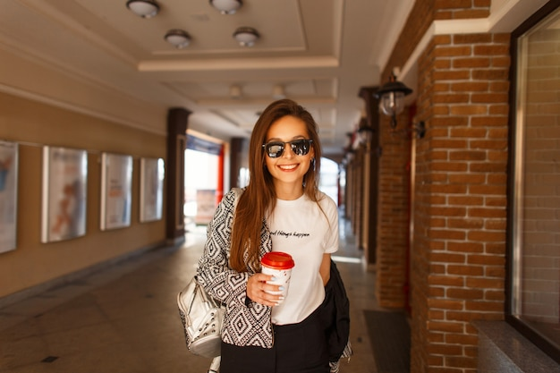 Femme heureuse à la mode avec des lunettes de soleil dans une veste de mode