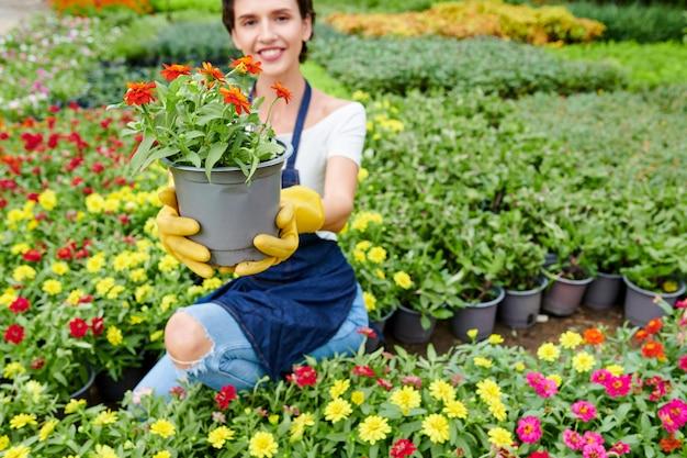 Femme heureuse montrant la plante qu'elle a cultivée