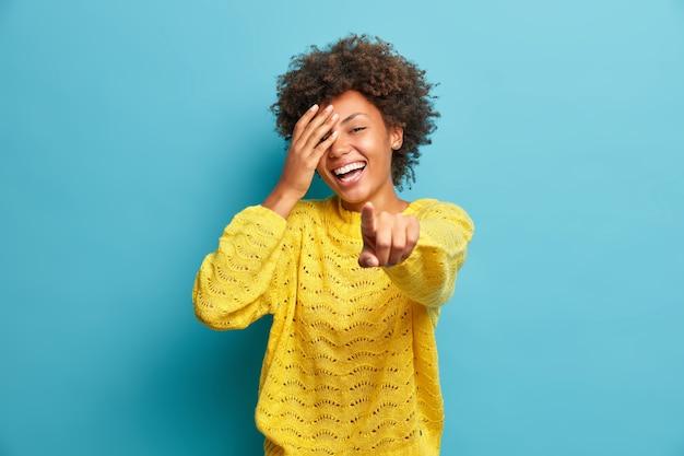 Une femme heureuse ne peut pas cacher les vrais points de bonheur directement à la caméra exprime la bonne humeur vêtue d'un pull décontracté exprime des émotions sincères voit quelque chose de drôle devant isolé sur bleu