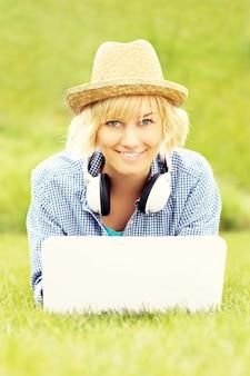 Une femme heureuse avec un ordinateur portable allongé sur l'herbe