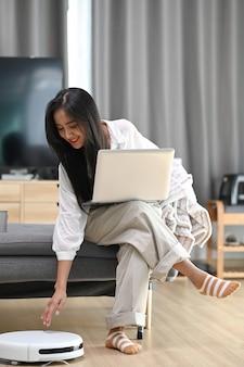 Femme heureuse avec un ordinateur portable assis sur un canapé et un robot aspirateur nettoyant la pièce à la maison.