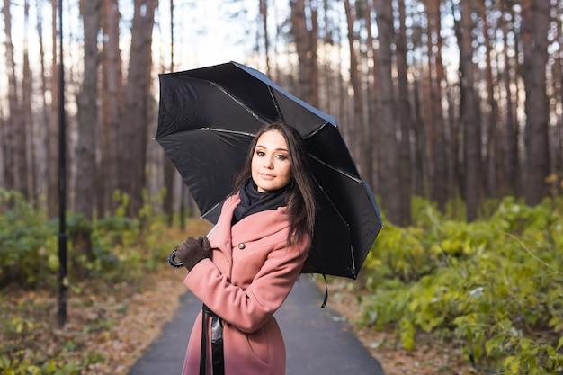 Femme heureuse avec parapluie sous la pluie pendant la promenade dans la nature automne