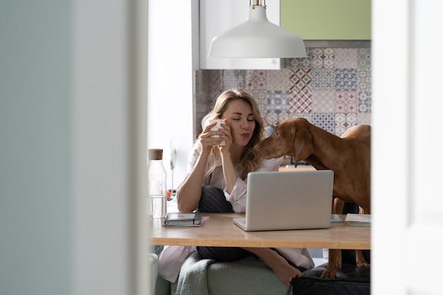 Une femme heureuse passe un appel vidéo à son mari en voyage d'affaires dans la cuisine avec un chien buvant du café