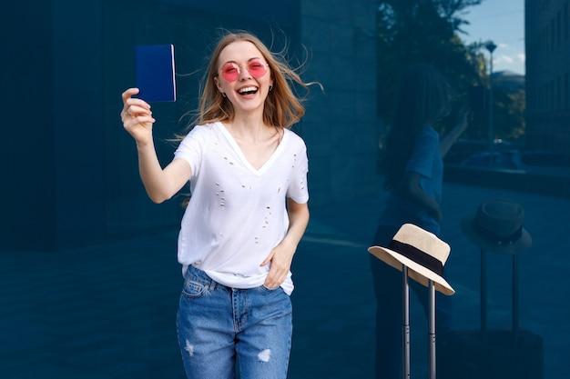 Femme heureuse avec passeport et bagages sur fond bleu