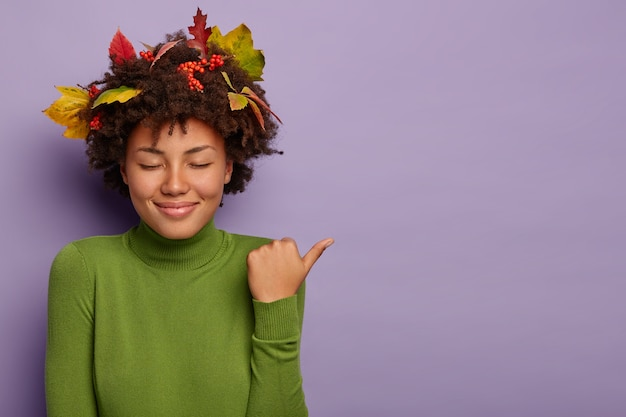 Une femme heureuse à la peau foncée ferme les yeux avec plaisir, sourit doucement, pointe le pouce vers l'extérieur, porte un col roulé vert, démontre une promo géniale