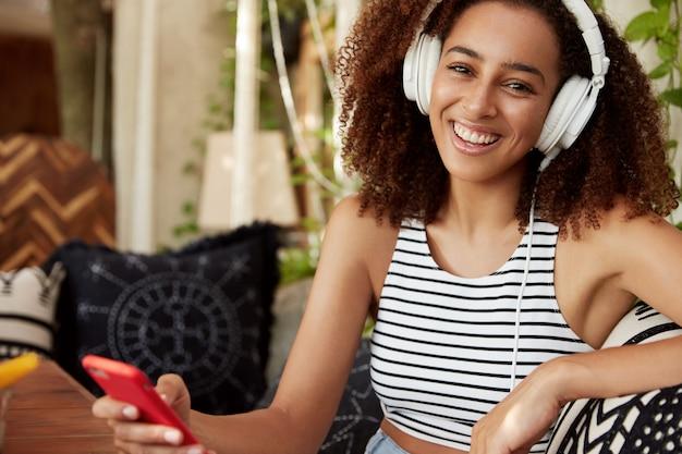 Une femme heureuse à la peau sombre écoute la chanson préférée dans les écouteurs, discute en ligne sur un téléphone intelligent, porte un t-shirt à rayures décontracté, télécharge des pistes populaires dans une liste de lecture. femme africaine divertit au café