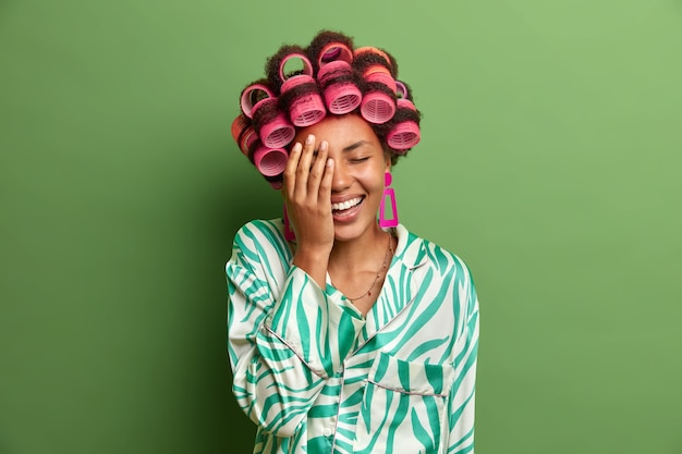 Une femme heureuse à la peau sombre fait la paume du visage, ne peut pas arrêter de rire après avoir entendu une blague, exprime des émotions positives, porte des bigoudis pour avoir l'air fabuleux à la fête de demain, vêtue d'une robe en soie. coiffure
