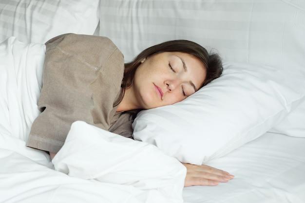Une femme heureuse en peignoir beige dort dans un lit moelleux avec une couverture étreignant des oreillers dans une chambre d'hôtel en gros plan