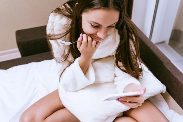 Une femme heureuse en peignoir est assise sur le lit et regarde le téléphone
