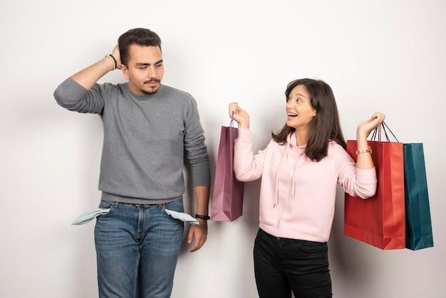 Femme heureuse et petit ami épuisé sur blanc.