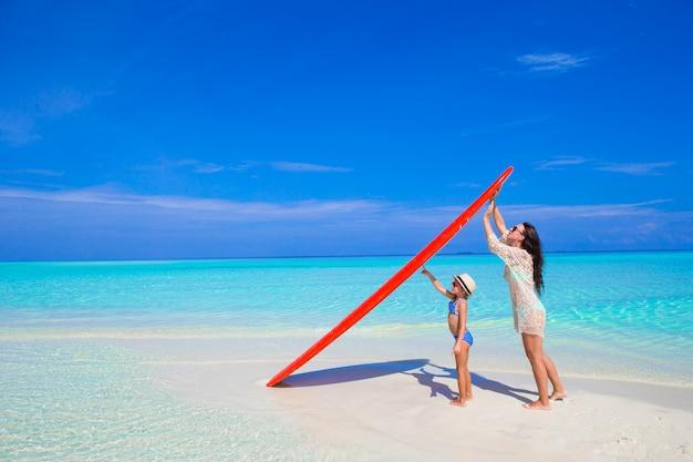 Femme heureuse et petite fille à la plage blanche avec planche de surf