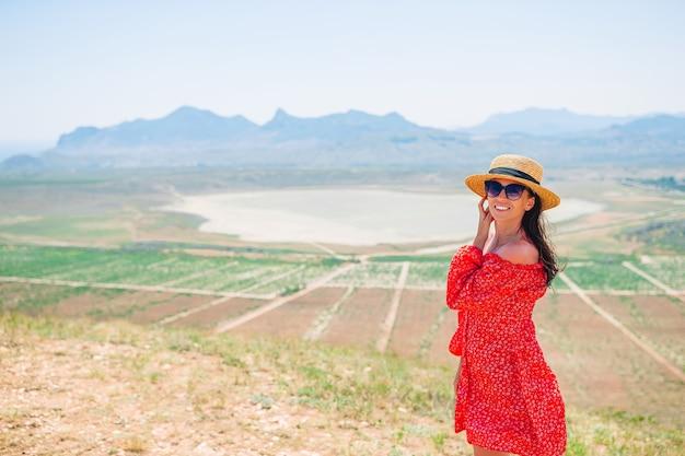 Femme heureuse en plein air sur le bord de la falaise en vacances d'été