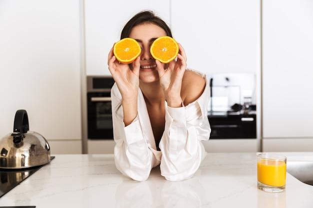 Femme heureuse portant des vêtements en soie tenant deux morceaux d'orange, pendant le petit-déjeuner dans la cuisine à la maison