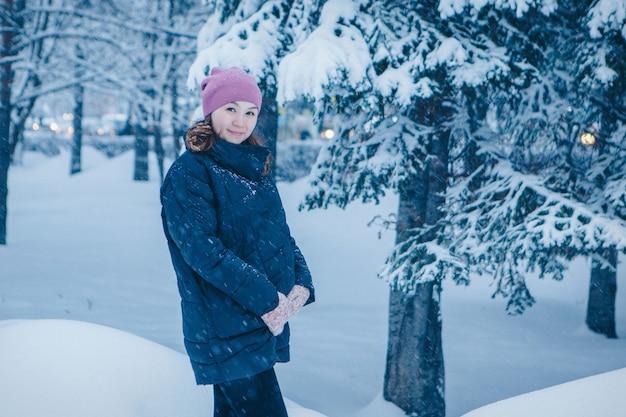Femme heureuse posant dans la forêt d'hiver
