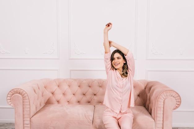 Femme heureuse posant avec les mains sur le canapé